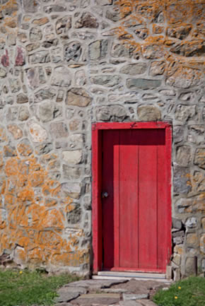 A bright red wooden door frames the entrance to a stone building